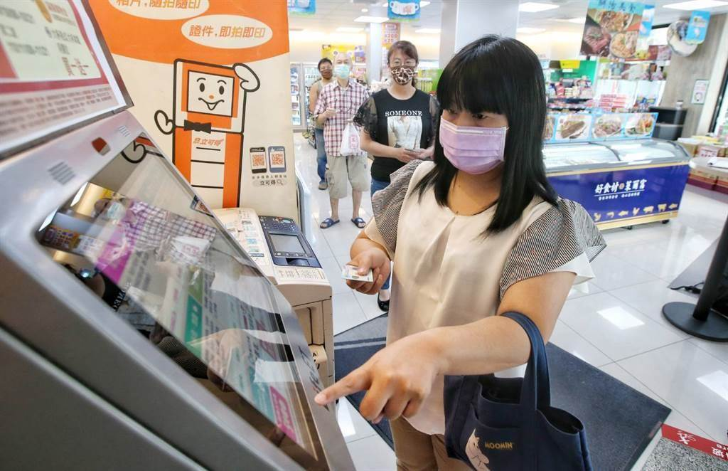 紙本五倍券於今(25)日上午9時開始接受預約,超商出現人潮在事務機進行預約。(趙雙傑攝)