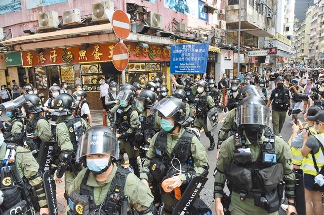 大陸外交部24日公布一份美國干預香港事務的清單,共5大類102條;要求美國停止干涉中國內政。圖為去年9月港警在油麻地街頭舉旗警告。(中新社)