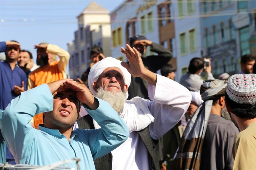 阿富汗西部大城赫拉特(Herat)25日驚見遺體高掛示眾,民眾抬頭查看。(圖/美聯社)