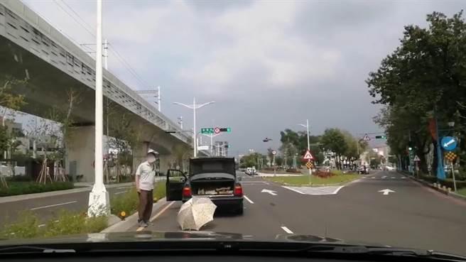 74歲的陳姓男子日前駕車行經東區復興東路段時,車子突然拋錨,手邊更只有一把雨傘充當警示牌。(台中市第三分局提供/馮惠宜台中傳真)