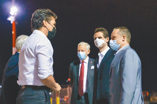 加拿大總理杜魯道(左)25日前往卡加立國際機場,迎接獲釋返國的康明凱及史佩弗。(摘自加拿大總理杜魯道官方推特)