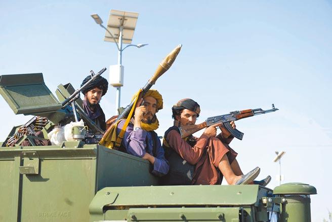 阿富汗塔利班25日在該國西部大城赫拉特擊斃4名綁匪後,將4人的遺體高掛示眾,藉此警告民眾勿以身試法。圖為塔利班成員乘坐軍事車輛行進在阿富汗坎大哈街頭。(新華社)