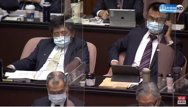 陳時中閉目養神,而一旁的陳吉仲則在講電話和看平板電腦。(圖片摘自中時新聞網Youtube)