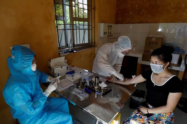 越南胡志明市爆出約有15萬例快篩結果為陽性仍待進一步清查、登載的病例,恐是疫情黑數。圖為一名醫護人員在越南峴港為一名女性採集血液樣本。(圖/路透)