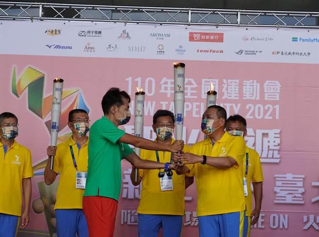 信義房屋執行協理黃茂書(圖中綠色上衣)代表台北市將全運會火炬傳給新北市長侯友宜。(圖/信義房屋提供)