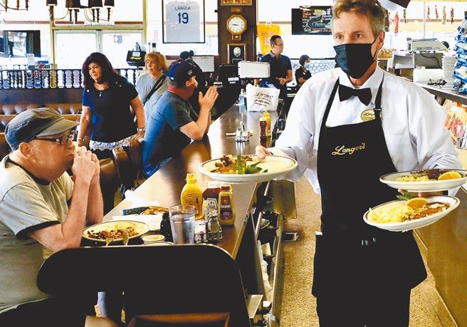 美國加州洛杉磯一家餐廳內,服務人員正在將餐點送到食客桌上。洛杉磯市議會通過新法令,規定成年顧客進入餐廳、酒吧、咖啡館、健身房、購物中心、博物館、電影院等室內公共場所,必須出示完成接種新冠疫苗的證明。(新華社資料照片)