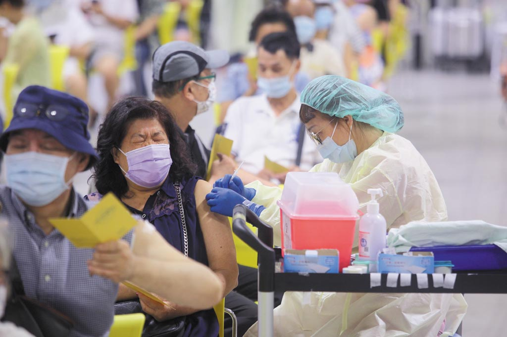 國內第12輪疫苗接種一口氣開放BNT、AZ及莫德納,疫情指揮中心也首度採兩階段接種,依不同廠牌採預約分流,圖為醫護人員為民眾施打疫苗。(張鎧乙攝)